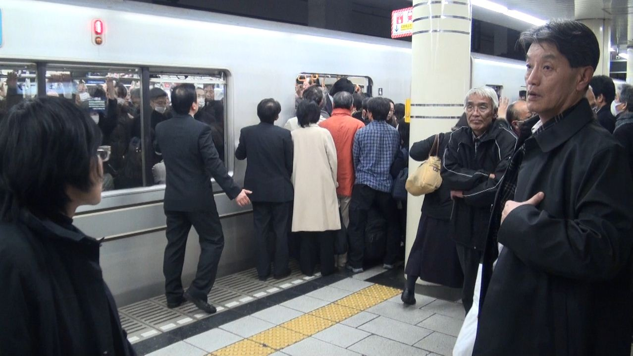 People entering a crowded Tokyo metro